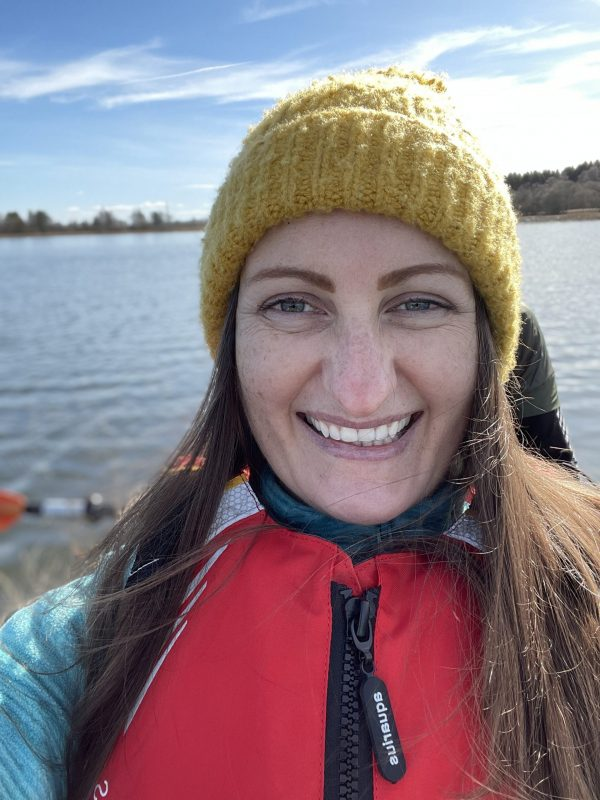 Anne Johnston wearing a yellow beanie and red life jacket on Forfar Loch