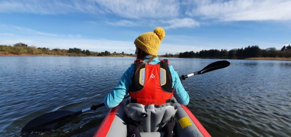 Anne Johnston paddling on Forfar Loch in a red Gumotex Solar inflatable kayak