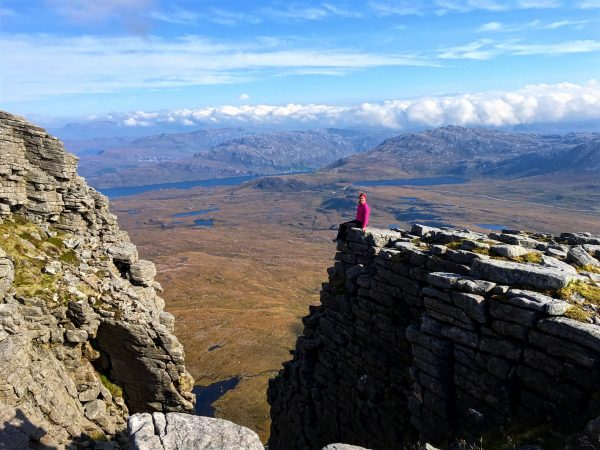 Anne Johnston sat on a rocky ledge on Quinag, Assynt